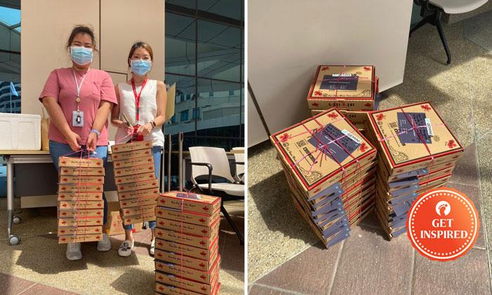 Tan Tock Seng Hospital staff (left)receiving pizzas from Gemini. PHOTOS: GEMINI